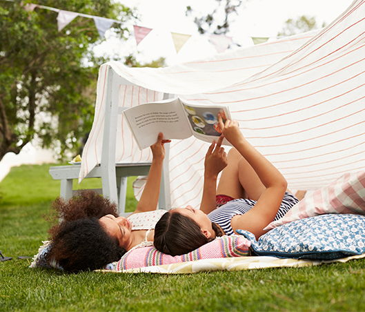 Mother with her young daughter lying on a blanket on the grass reading a children's book
