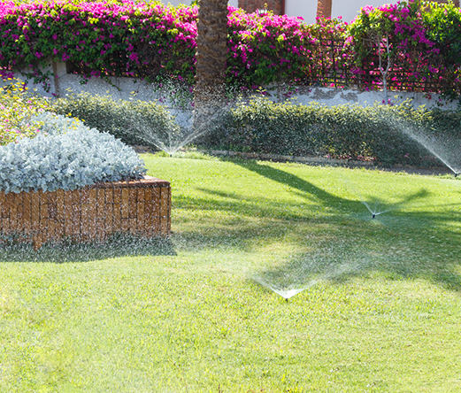 multiple sprinkler heads spraying water on a lawn
